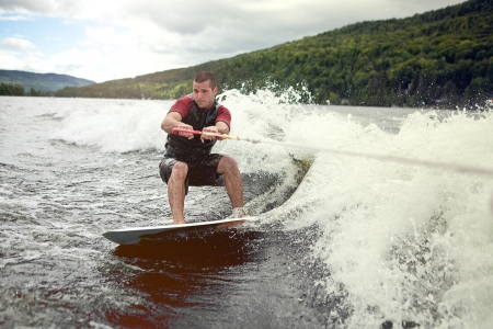 Happy handsome man wakesurfing in a lake and pulled by a boat