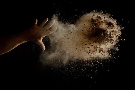 splatter: Lanzar un puñado de tierra marrón en el aire - aislados en fondo negro Foto de archivo