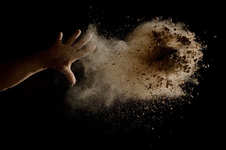 Throwing a Handful of brown earth in the air - isolated on black background Stok Fotoğraf