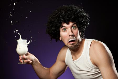 그는 밤에 우유 한 잔을 마시고 whle 잡힌 수염을 가진 남자 스톡 콘텐츠