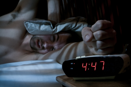 Unhappy sleeping man smashing the alarm clock in the morning  very early   Banco de Imagens