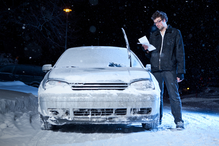 Man upset after getting a night parking ticket during the winter Archivio Fotografico