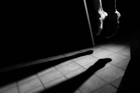 Barefoot Hangman at night in the door frame  Sad conceptual image representing suicide  photo