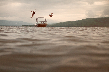 Two Young Man Jumping of a Boat and doing flips photo