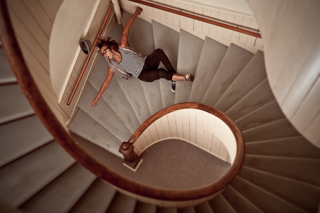 Young man falling down into the steep spiral staircase