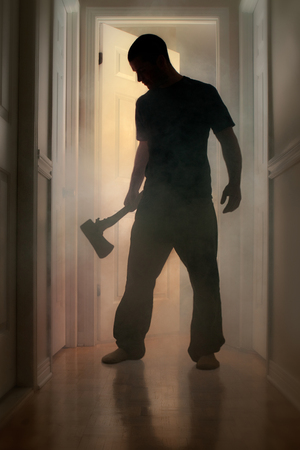 Epic concept with man in silhouette holding axe inside a smoking house at night photo