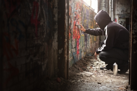 Illegal Young man Spraying black paint on a Graffiti wall. (room for text)