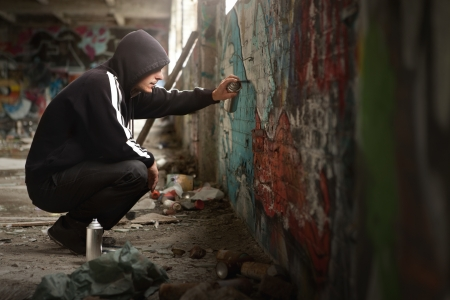 graffiti: Illegal Young man Spraying black paint on a Graffiti wall. (room for text)