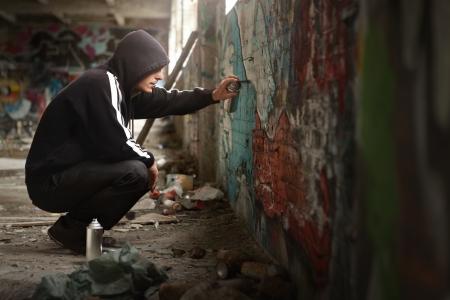 Joven ilegal pulverización de pintura negro en una pared pintada. (Espacio para texto)