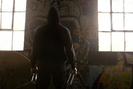 facing a wall: Young man wearing a Hoody Facing a wall and ready to do a Graffiti