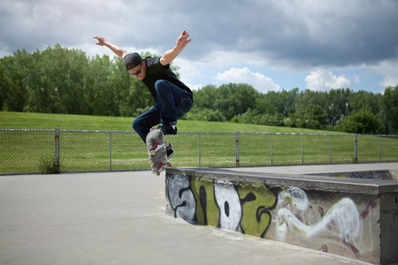 Young Skateboarder doing a Wallie in a skatepark photo