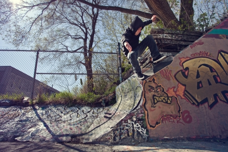 Young Skateboarder doing a Wallie on a Graffiti wall Archivio Fotografico