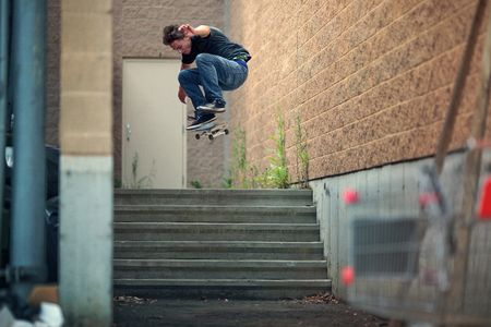Young Skateboarder doing a Kickflip down the stairs