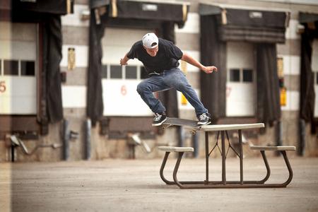 grind: Skater joven que hace una rutina torcida en una mesa de picnic