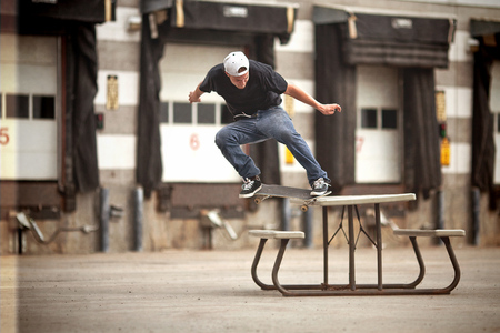 skateboard: Young Skateboarder doing a Crooked Grind  on a Picnic table