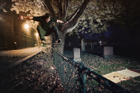 Young Skateboarder doing a Ollie trick over a Fence at night photo
