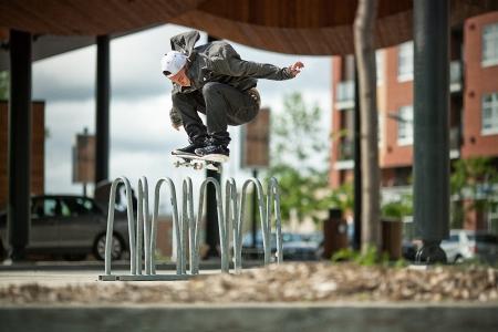 オリー上の自転車ラックをやっている若いスケートボーダー