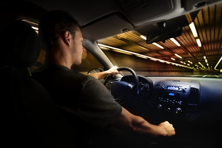 Young Adult Driving Over the Speed Limit in a Tunnel. View from inside the car. photo