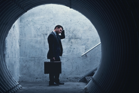 Desparate Businessman Standing and holding his head in a dark tunnel. With room for your text Reklamní fotografie