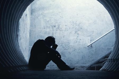 Empresario Desparate en silueta en el suelo y con la cabeza en un túnel oscuro. Con espacio para el texto Foto de archivo