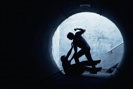 violencia: Hombre joven que es asaltado en un t�nel oscuro por un hombre violento Foto de archivo