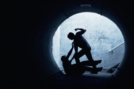 Young man being mugged in a dark tunnel by a violent man Stock Photo
