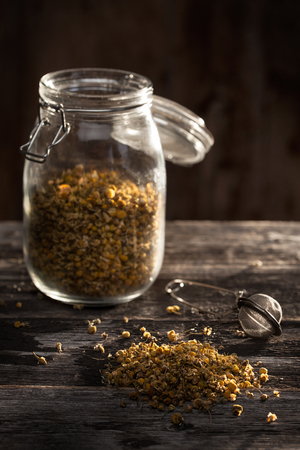 dried chamomile flowers and tea-strainer on a wood table photo