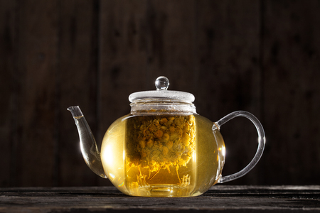Ready and Hot Chamomile Tea in a Clear teapot on a Wood Table photo