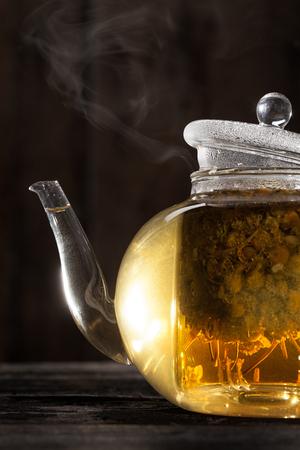 vapore acqueo: Pronta e calda Camomilla tè in una teiera trasparente su una tavola di legno