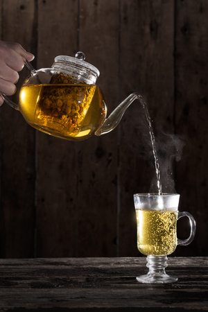 Pouring Hot Chamomile Tea in a clear Glass photo