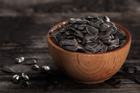 sunflower seeds: Close-up of Sunflower Sprouting Seeds in a Wooden bowl Stock Photo