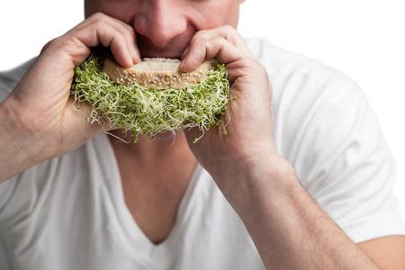 Young Adult Eating a Sandwich Full of Alfalfa Sprouts (healthy lifestyle concept) Archivio Fotografico