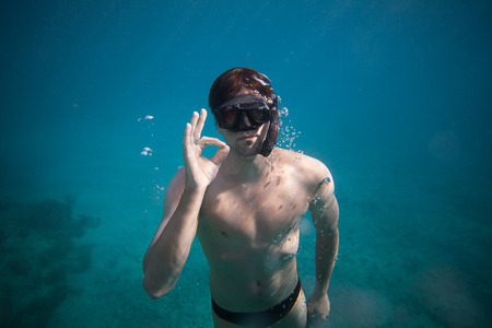 freediver: Freediver doing the Okay Sign Underwater
