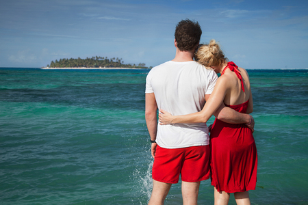Couple Loking at The Sean with Desert Island in Background photo