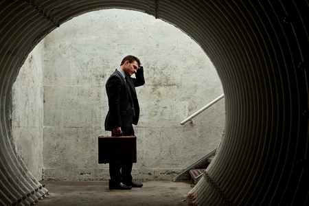 Desparate Businessman Standing and holding his head in a dark tunnel. With room for your text Standard-Bild
