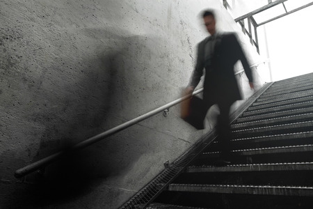 room for your text: Busy Businessman Rushing Down the Stairs. Motion blur to show the speed and room for your text.