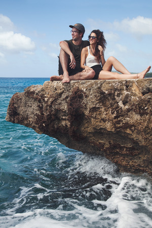Beautiful Couple sitting on a rock and Looking at The View in San Andres Island, Colombia