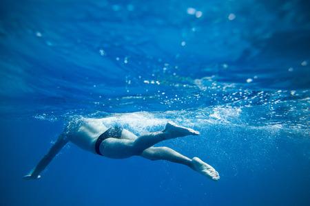 Natación del hombre solo en el mar azul profundo photo