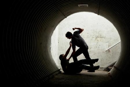 Hombre joven que es asaltado en un túnel oscuro por un hombre violento photo