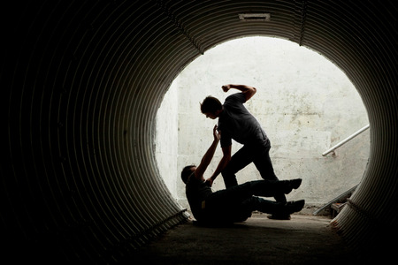 aggressive people: Young man being mugged in a dark tunnel by a violent man Stock Photo