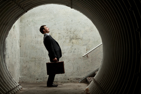 Funny Businessman side view in a tunnel with a Briefcase