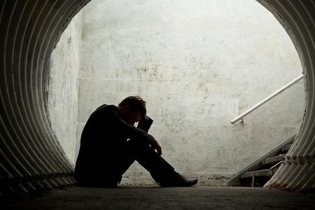 실루엣이 바닥에 누워 어두운 터널에 그의 머리를 들고있는 절망적 사업가. 텍스트를위한 공간