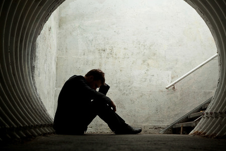 Desparate Businessman in silhouette lying on the ground and holding his head in a dark tunnel. With room for your text