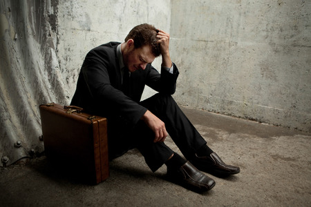 Desparate Businessman lying on the ground and holding his head in a dark tunnel. With room for your text