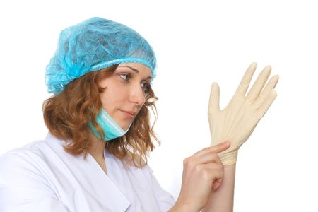 Female doctor in uniform and medical mask pulling on surgical gloves photo