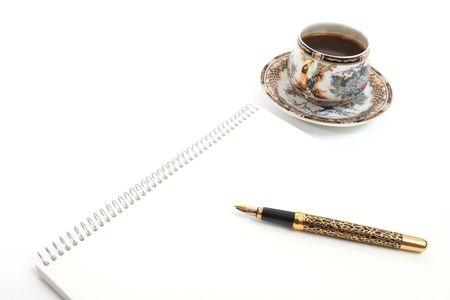 Golden Pen on notebook and cup of coffee photo