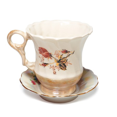 ancient teacup on saucer decorated with gold and roses Stock Photo