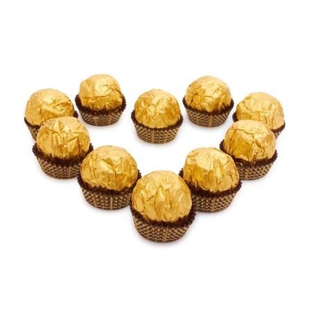 Candy in golden foil in the shape of a heart. Isolated on white photo