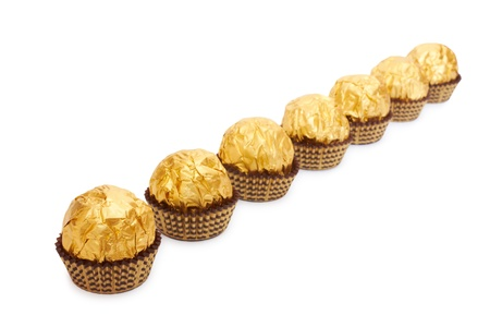Candy in golden foil. Isolated on white photo