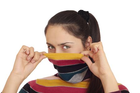 pulling faces: Attractive green-eyed woman pulling turtleneck sweater over her face isolated over white